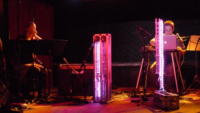 Troy Rogers performs behind the illuminated pink columns of the robotic musical instruments AMI and CARI, which form Expressive Machines Musical Instruments' (EMMI) MARIE, with Dana Jessen of the EAR Duo at the Southern in Charlottesville, VA