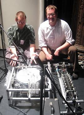 Composers Troy Rogers and Steven Kemper at NIME 2009 with robotic musical instruments PAM (Poly-tangent Automatic (multi-)Monochord) and MADI (Multi-mallet Automatic Drumming Instrument). These musical robots were designed and built by Expressive Machines Musical Instruments (EMMI).