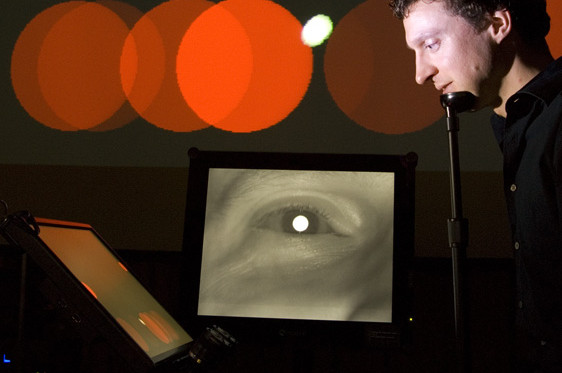 Anthony Hornof performs EyeMusic, a musical and multimedia work composed by Troy Rogers with Hornof and Tim Halverson, in which eye movements are sensed with the aid of an eye tracker and mapped to audio and visual control parameters. Photo credit: Anthony Hornof