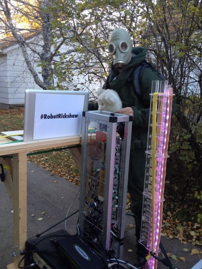 Robot Rickshaw, a cart full of robotic musical instruments piloted by a lunatic in a hazmat suit+teddy bear, prepares to embark upon a walk in Duluth, MN. Photo credit: Melissa Maki