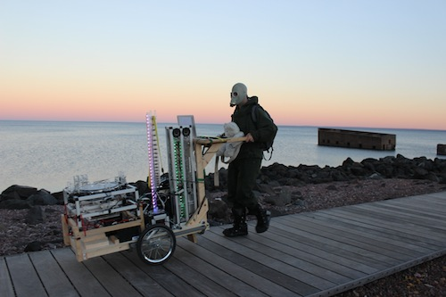 Robot Rickshaw: a cart full of robotic musical instruments piloted by a lunatic in a hazmat suit+teddy bear, being walked along the Lakewalk in Duluth, MN. Photo credit: Melissa Maki