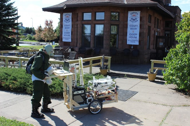 Robot Rickshaw robotic musical instruments perform at BradtoberFest 2014 in front of Endion Station Public House in Duluth, MN. Robot Rickshaw is a rapidly-deployable, human-driven, two wheeled cart full of robotic musical instruments (robots that play music). Piloted by a lunatic in a hazmat suit+teddy bear. Very popular for festivals, children's parties, funeral processions, and more! Photo credit: Melissa Maki